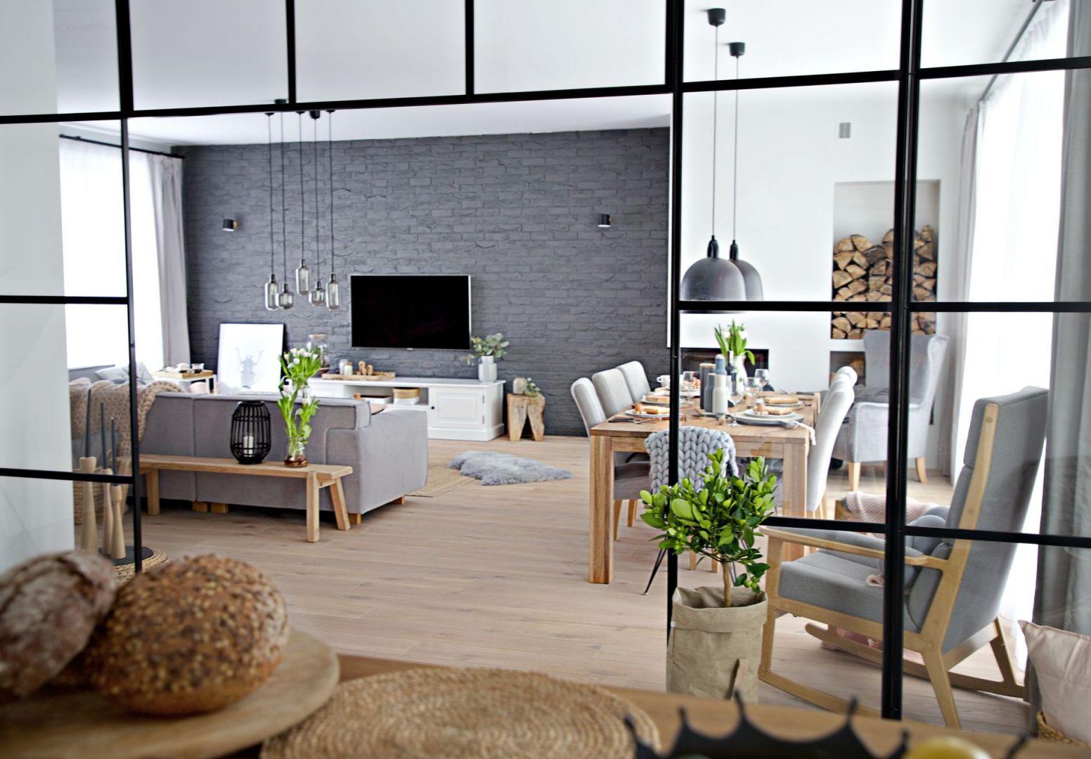 W salonie, który jest otwarty na jadalnię, sprawdzą się meble, które można ustawić na środku jako oddzielenie strefy wypoczynku. Projekt wnętrza: SHOKO design