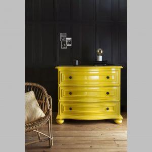 Komoda pomalowana na kolor żółty pięknie wyróżnia się na tle czarnej ściany. Fot. Liberon