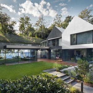 Dom został zaprojektowany tak, aby jak najlepiej wpisać się w istniejące otoczenie pasa brzegu nadmorskiego oraz naturalnie uformowanych skarp, które w dużym stopniu pokryte są zielenią. Projekt i zdjęcia: Arch-Deco