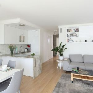 W otwartym salonie ściany wykończono białą farbą oraz białą cegłą, dzięki czemu całość jest jasna i nowoczesna. Projekt: Laura Sulzik. Fot. Bartosz Jarosz