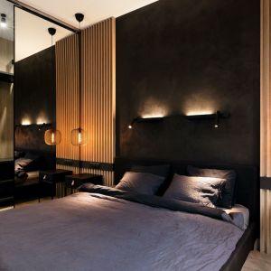 Ścianę zdobi elegancka czerń, która doskonale łączy się z drewnianymi paneli oraz lustrem, skrywającym wygodną garderobę. Projekt: Anna Gostomczyk, pracownia 2form. Fot. Norbert Banaszyk