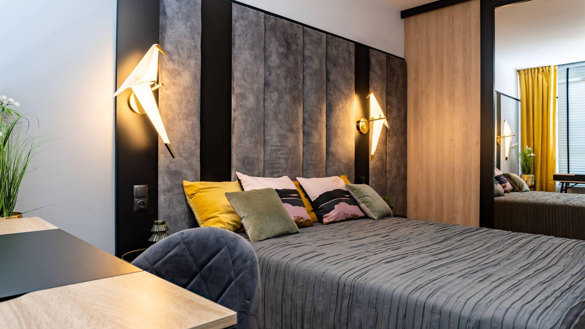 Ścianę za łóżkiem zdobi piękny, tapicerowany zagłówek w szarym i czarnym kolorze. Projekt: DG Studio Donata Gadalska. Fot. Jacek Fabiszewski