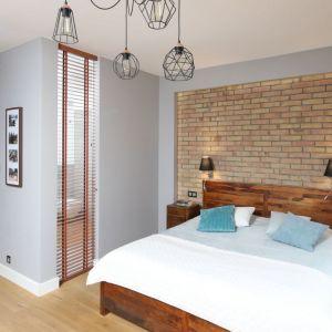 Ścianę za łóżkiem wykończono cegłą w ciepłym, brązowym odcieniu. Projekt: Maciejka Peszyńska-Drews. Fot. Bartosz Jarosz