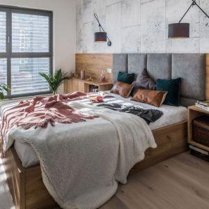 Ścianę za łóżkiem wykończono drewnem oraz farbą imitująca beton. Projekt i zdjęcia: Kodo Projekty i Realizacje Wnętrz