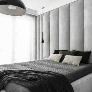 Tapicerowany zagłówek w jasnym szarym kolorze stanowi piękną dekorację ściany za łóżkiem. Projekt: Anna Maria Sokołowska. Fot. Fotomohito