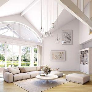 Na środku, w centralnym miejscu domu, mamy piękny, wysoki salon z dużym oknem na taras i ogród. Projekt: arch. Michał Gąsiorowski. Fot. MG Projekt