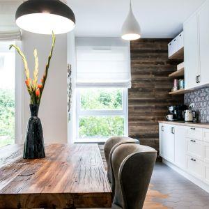 Rysunek drewna zdobi zarówno kuchenny blat, jak i podłogę w części salonowo - jadalnianej.