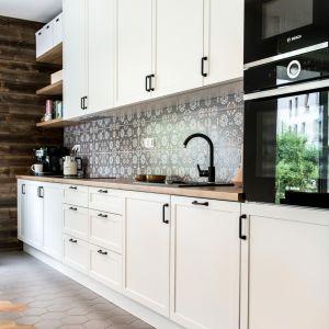 Podobnym stylistycznie zabiegiem jest urządzenie na tle białej, klasycznej zabudowy meblowej jadalni utrzymanej w konwencji loftów.