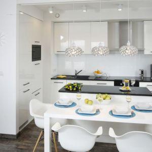 Stół jadalniany został ustawiony tuż przy wyspie kuchennej. Całą przestrzeń urządzono w bieli. Projekt: Katarzyna Uszok. Fot. Bartosz Jarosz