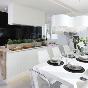 Duży, rodzinny stół ustawiono przy wyspie kuchennej. Wnętrze urządzono bardzo spójnie. Projekt: Dariusz Grabowski. Fot. Bartosz Jarosz