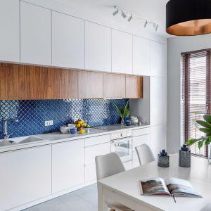 Kuchnię i jadalnię urządzoną w bieli pięknie ożywiają płytki w kobaltowy kolorze, którymi wykończono ścianę nad blatem. Projekt: Monika Pniewska. Fot. Marta Behling/Pion Poziom
