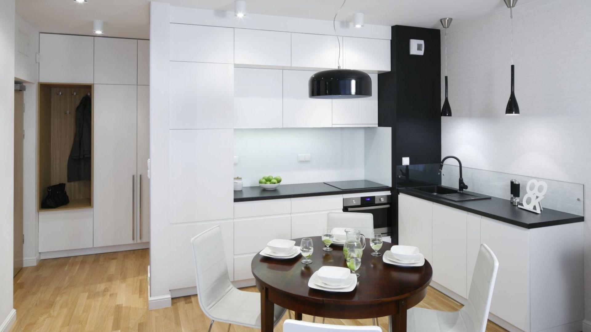 Przy niedużym aneksie kuchennym zaplanowano równie niedużą jadalnię. Kontrast bieli i czerni prezentuje się bardzo elegancko. Projekt: Ewa Para. Fot. Bartosz Jarosz