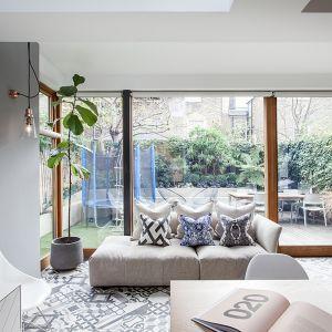 Przestrzeń outdoorowa śmiało wkracza do wnętrza otwartego na kuchnię salonu. Projekt Tamara Tymowski Sybaris Design/ Zajc