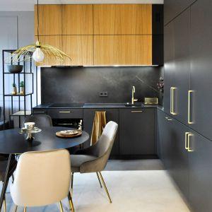 Aneks kuchenny z ciemnymi frontami zestawionymi  z naturalnym drewnem i złotymi dodatkami. Projekt i zdjęcia: studio Mauve