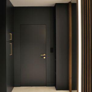 Czarny kolor pojawia się także na ścianach w przedpokoju, gdzie zestawiono go z modnymi drewnianymi lamelami. Projekt i zdjęcia: studio Mauve
