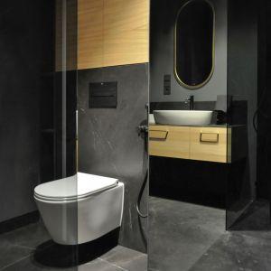 Czarna łazienka to sprawdzony sposób na elegancję i stylowe wnętrze. W tej jasne drewno połączono ze złotem i oczywiście czernią. Projekt i zdjęcia studio Mauve