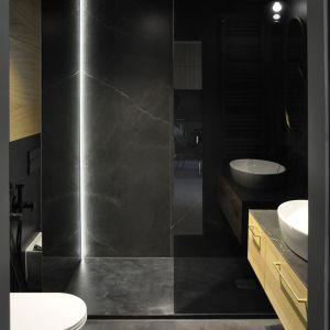 Czarne wnętrze może wydawać się większe niż jest w rzeczywistości. Czarne płytki łazienkowe połączono tu ze złotymi dodatkami. Projekt i zdjęcia studio Mauve