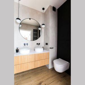 Ściana nad wc to funkcjonalna zabudowa meblowa w matowym czarnym kolorze. Projekt Sandra Maculewicz. Fot. Łukasz Pepol