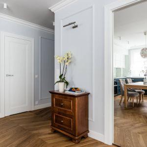 W mieszkaniu uwagę przyciągają piękne detale takie jak stolarka drzwiowa, uchwyty meblowe czy posadzka w przedpokoju z czarną bordiurą. Projekt: Magdalena Bielicka, Maria Zrzelska-Pawlak. Fot. Fotomohito