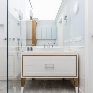 Duże lustro optycznie powiększa przestrzeń łazienki. Pięknie prezentuje się szafka pod umywalkę na drewnianych nogach. Projekt: Magdalena Bielicka, Maria Zrzelska-Pawlak. Fot. Fotomohito