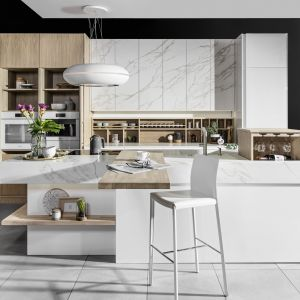 Biała kuchnia z dekorem marmuru i drewna prezentuje się niezwykle efektownie. Wyspa podkreśla jej luksusowy charakter. Fot. Halupczok