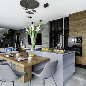 W urządzonej w szarościach i drewnie otwartej strefie dziennej kuchnia, salon i jadalnia wzajemnie się przeniakają tworząc spójną stylistycznie całość. Projekt Agnieszka Morawiec. Fot. Dekorialove.