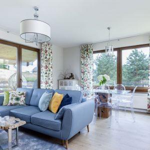 Na środku salonu ustawiono kanapę w pięknym niebieskim kolorze. Przytulny klimat wprowadzają do wnętrza również zasłony w piękne wzory. Projekt: Justyna Mojżyk, poliFORMA. Fot. Monika Filipiuk-Obałek