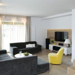 Żółty fotel doskonale pasuje do ciemnych, szarych kanap. Stanowi ładny kontrast. Projekt: Małgorzata Galewska. Fot. Bartosz Jarosz
