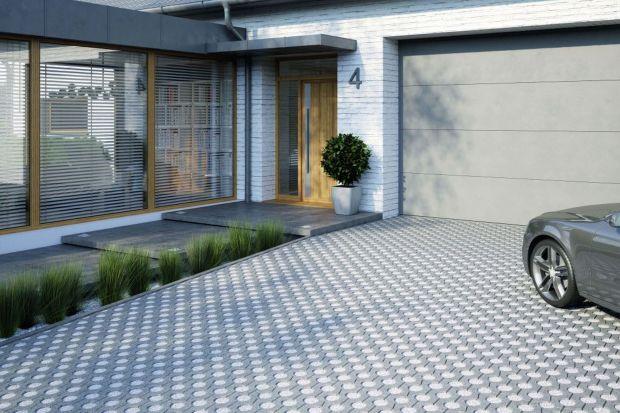Nie zawsze podjazd do przydomowego garażu musi być jednolitą nawierzchnią. Może być też … zielonym dywanem prowadzącym wprost na posesję. Do stworzenia takiej aranżacji doskonale nadają się ażurowe płyty betonowe, w których otworach możn