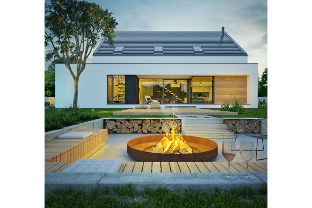 Projekt nowoczesnego domu z dużym, wygodnym i zadaszonym tarasem. Budynek pięknie wpisuje się zarówno w naturalne, jak i miejskie otoczenie.