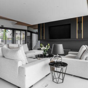 Przeciwwagą dla jasnych kolorów zastosowanych w salonie pozostaje ściana telewizyjna utrzymana w odcieniach czerni, wzbogacona delikatnymi złotymi detalami. Projekt: Joanna Ochota. Fot. Mateusz Kowalik