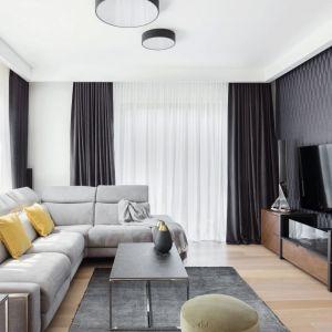 Salon, będący częścią otwartej strefy dziennej, jest nowoczesny, jasny i przytulny. Szarości pięknie łączą się z drewnem, które z kolei ożywiają dodatki w żółtym kolorze. Projekt: Katarzyna Maciejewska, Maciejewska Design. Fot. Anna Laskowska, Dekorialove