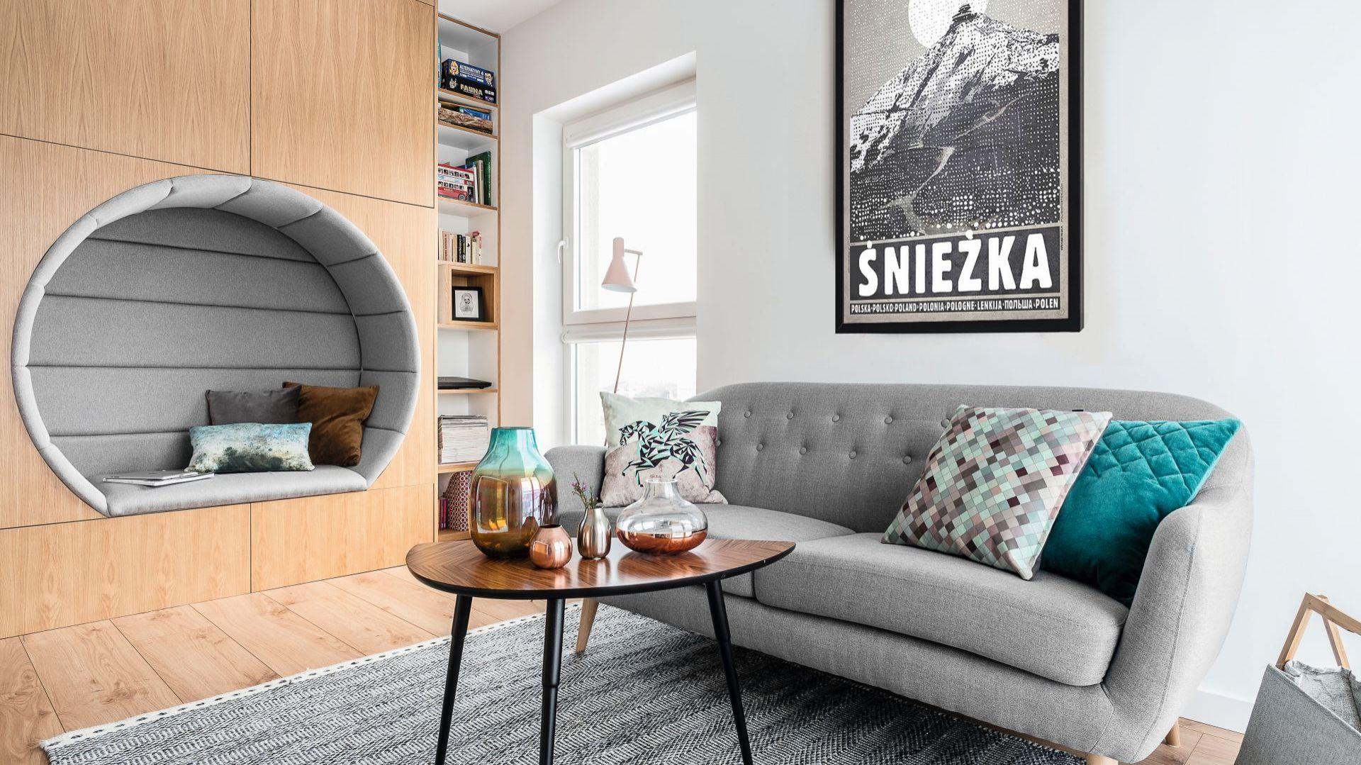 W małym salonie zdecydowano się na niewielką, ale stylową sofę na nóżkach, które dodają jej lekkości. Projekt Magdalena Bielicka, Maria Zrzelska-Pawlak, Pracownia Magma. Zdjęcia Fotomohito