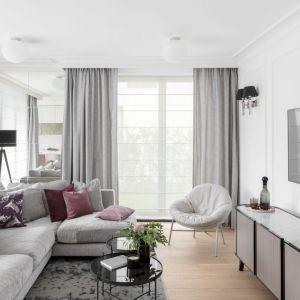 W centrum salonu stanęła jasna, narożna sofa oraz miękki fotel. Wykonane na indywidualne zamówienie, duże lustro na ścianie obok sofy pozwoliło powiększyć optycznie wnętrze. Projekt: JT Grupa. Fot. ayuko studio