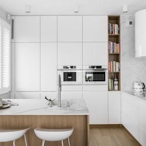 Białą kuchnię połączono z subtelnie wprowadzanymi dekorami drewna i marmuru. Projekt Maka Studio