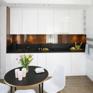 Białą kuchnię ociepla drewno. Czarny blat podkreśla czystość bieli. Projekt Małgorzata Galewska