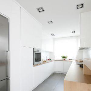 Biała kuchnia doskonale wyeksponuje sprzety AGD w kolorze inox. Projekt Joanna Ochota