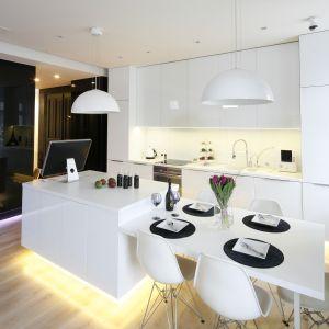 """Kuchnia """"all in white"""" doskonale kontrastuje z czarnym tłem zabudowy salonowej. Projekt Joanna Scott, Małgorzata Muc"""
