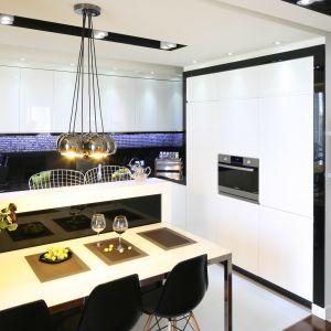 Biel frontów kuchennych podkreślają czarne ramy i efektowne oświetlenie. Projekt Małgorzata Mazur
