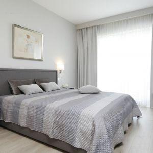 Kwadratowe kinkiety w białym kolorze zdobią szarą ścianę za łóżkiem. Na Projekt: Katarzyna Uszok. Fot. Bartosz Jarosz