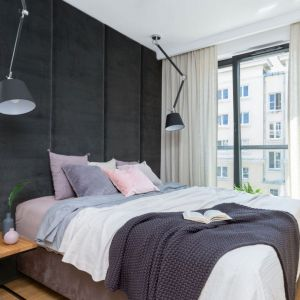 Dwie czarne lamy wiszące są bardzo praktyczne i dekoracyjne. Doskonale pasują do tapicerowanej ściany za łóżkiem. Projekt: Decoroom. Fot. Pion Poziom