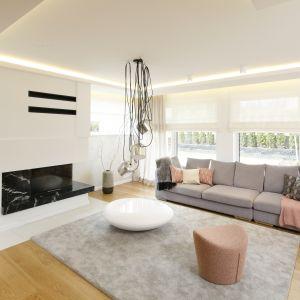 W dużym salonie jasna, szara kanapa zachęca do wypoczynku. Projekt Agnieszka Hajdas-Obajtek