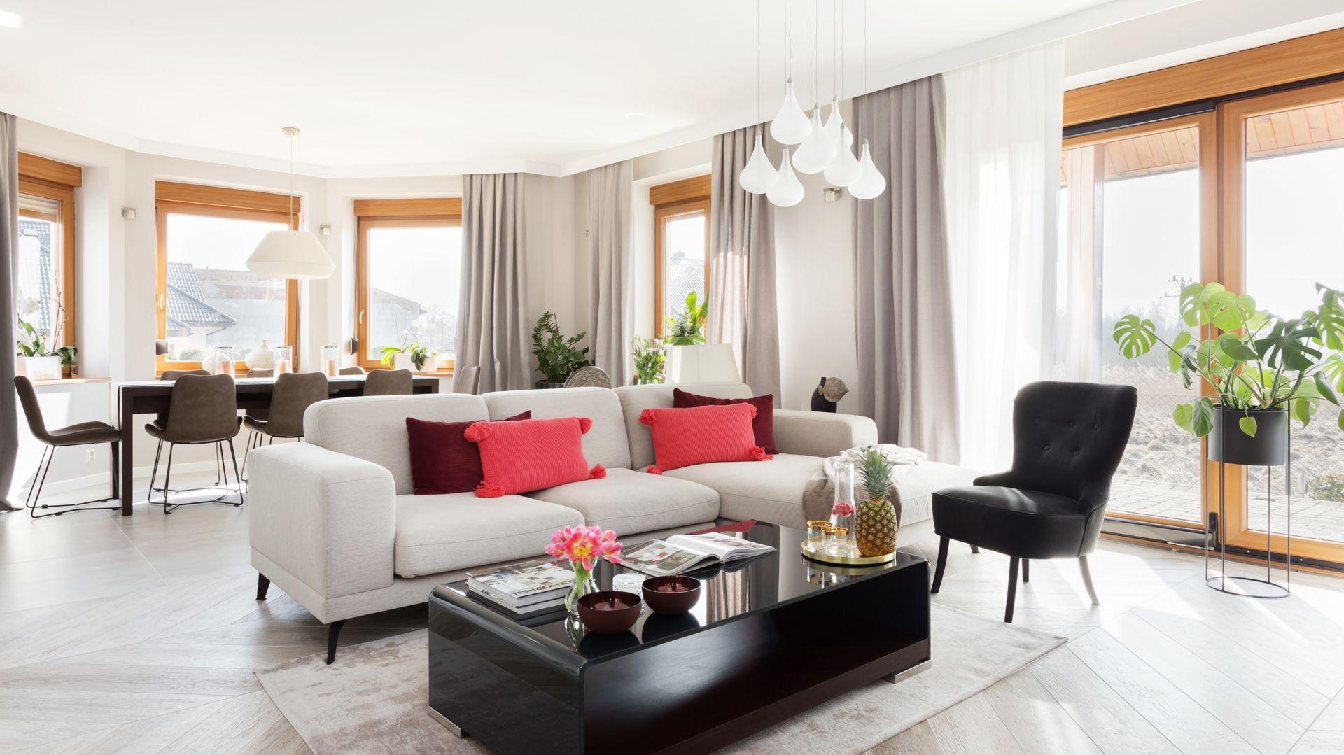 W salonie w domu jednorodzinnym wygodna kanapa optycznie oddziela przestrzeń wypoczynkową od jadalnianej. Projekt Katarzyna Maciejewska. Fot. Dekorialove