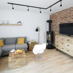 Przytulny wystrój salonu buduje połączeni cegły i drewna. Projekt Katarzyna uszok