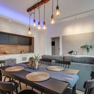 Duży stół jadalniany ustawiono tuż za kanapą, wydzielając tym samym dwie odrębne strefy w otwartej przestrzeni. Projekt Małgorzata Mataniak-Pakuła. Fot. Radosław Sobik
