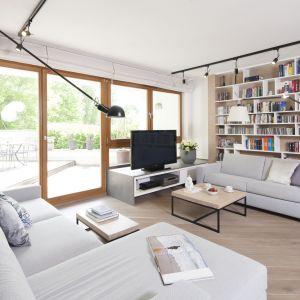 W przestronnym salonie cała ściana została przeznaczona na domowy księgozbiór. Projekt Katarzyna Kiełek