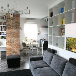 Stylowy salon oferuje sporo otwartych półek na książki i dekoracje. Projekt Agnieszka Ludwinowska