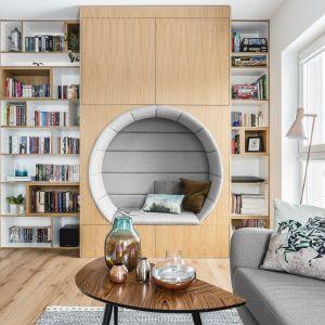 """Regał na książki połączono z wykonaną na zamówienie zabudową z """"dziuplą"""" - idealnym miejscem na lekturę. Projekt Magma. Fot. Fotomohito"""