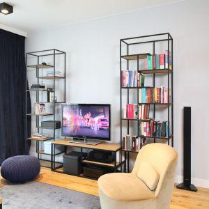 Proste, metalowe regały doskonale wpisują się w loftowy klimat salonu. Projekt Maciejka Peszyńska-Drews