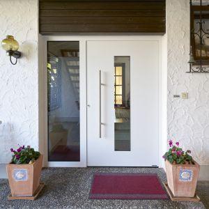Po zamontowaniu nowoczesnych aluminiowych drzwi wejście do domu jest jaśniejsze i bardziej przyjazne, a do wnętrza wpada więcej naturalnego światła. Właściciele doceniają też dobrą izolację cieplną i wysoką ochronę przed włamaniem, jaką daje standardowe wyposażenie przeciwwłamaniowe w klasie RC 3. Stare drzwi zamienione zostały na nowe w ciągu zaledwie jednego dnia. Na zdj. ThermoSafe firmy Hörmann